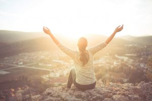 carefree-happy-woman-sitting-on-top-of-mountain-edge-cliff-enjoying-sun-on-her-face-raising-hands-in-sunlight-rays-enjoying-nature-66973352